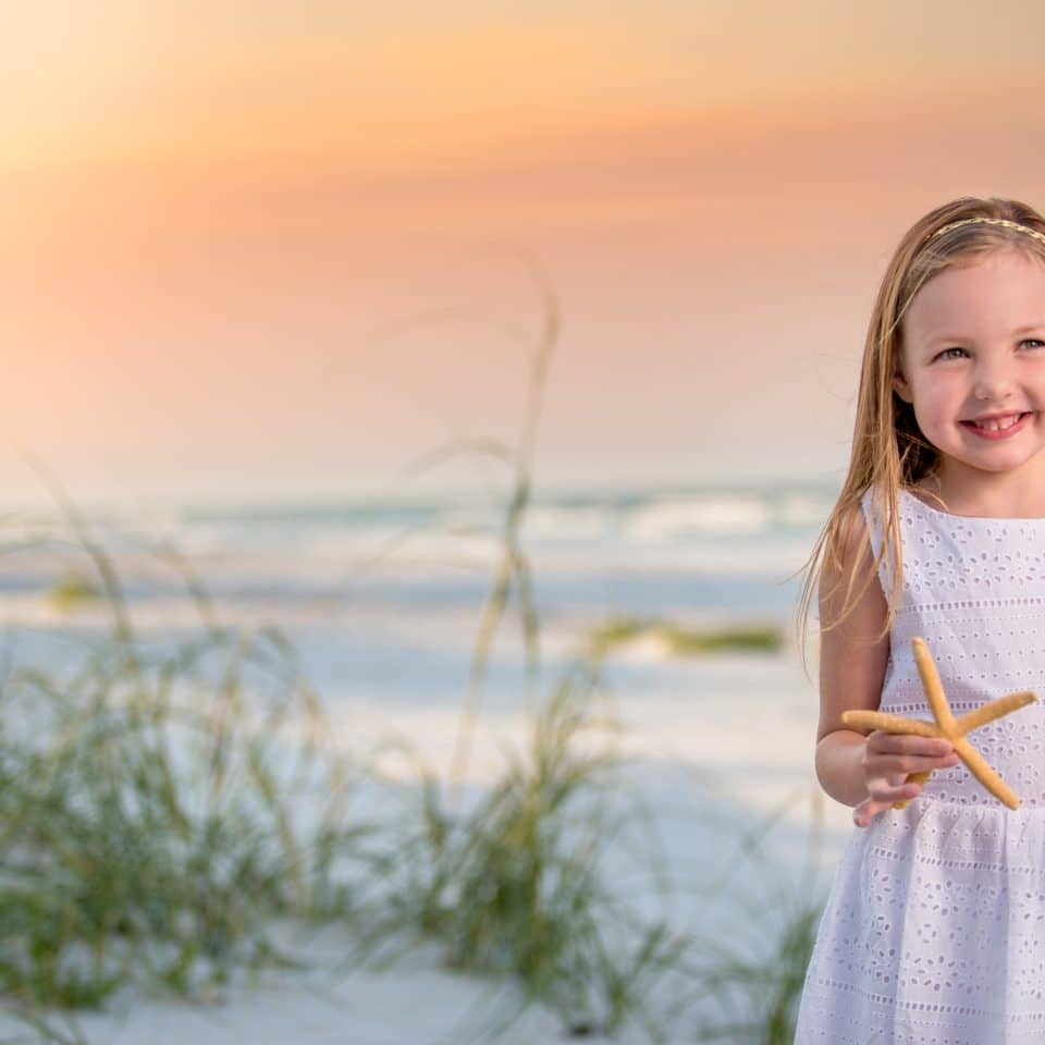 New Smyrna beach photographer captures a portrait of a child on new Smyrna beach at sunset holding a starfish
