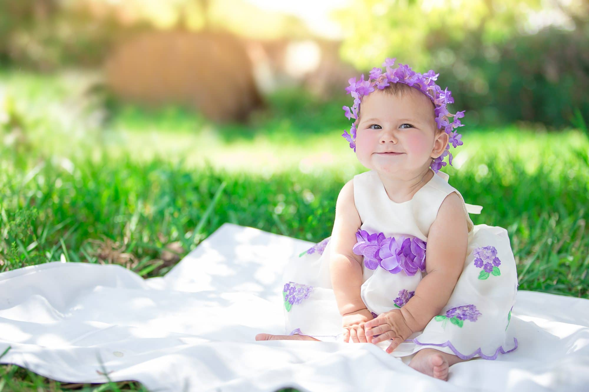 Baby in purple easter dress posing for an easter photography session with an orlando photographers