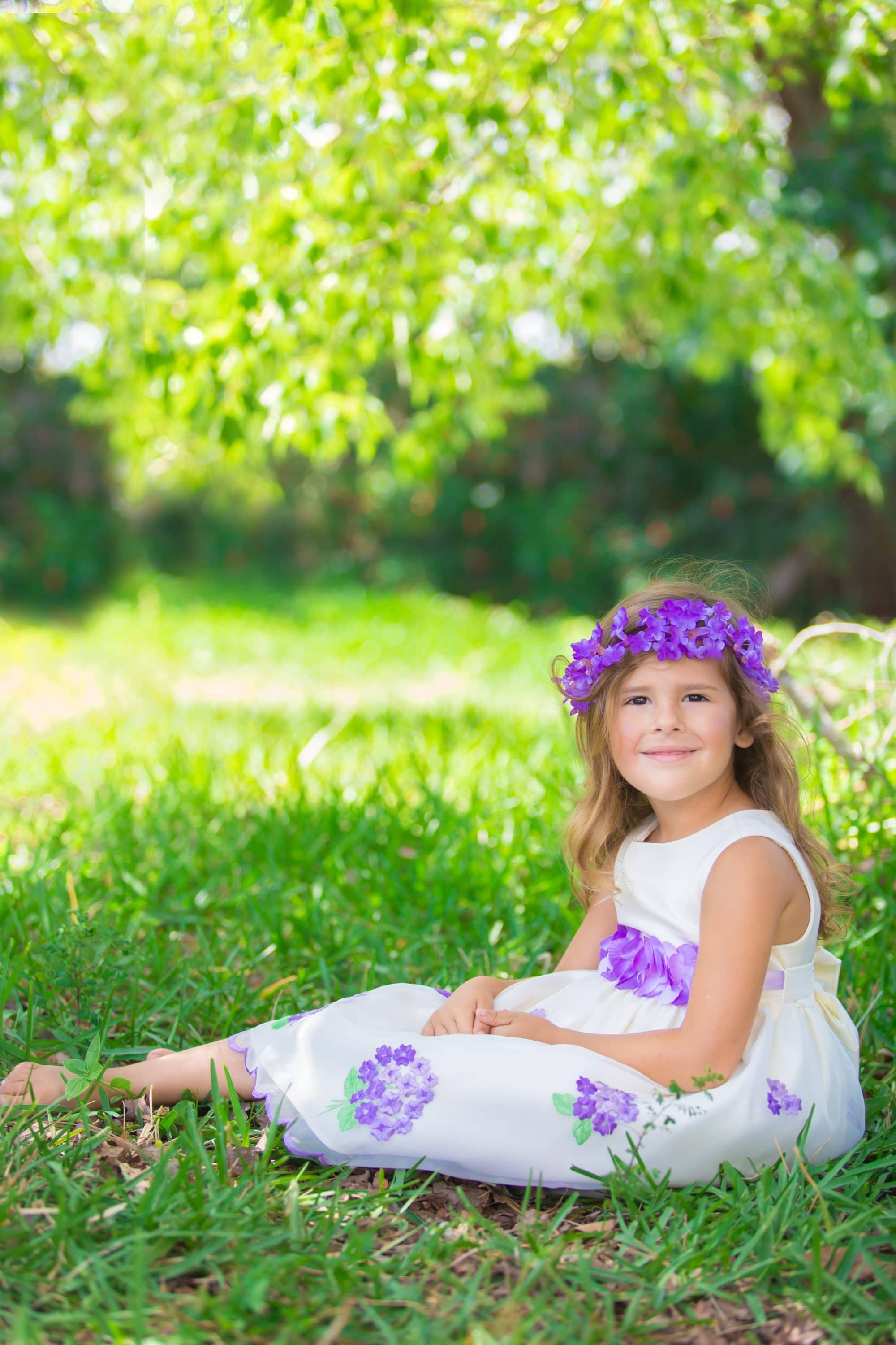 Orlando children photographer photographs a girl wearing a purple Easter dress for a spring family portrait session.
