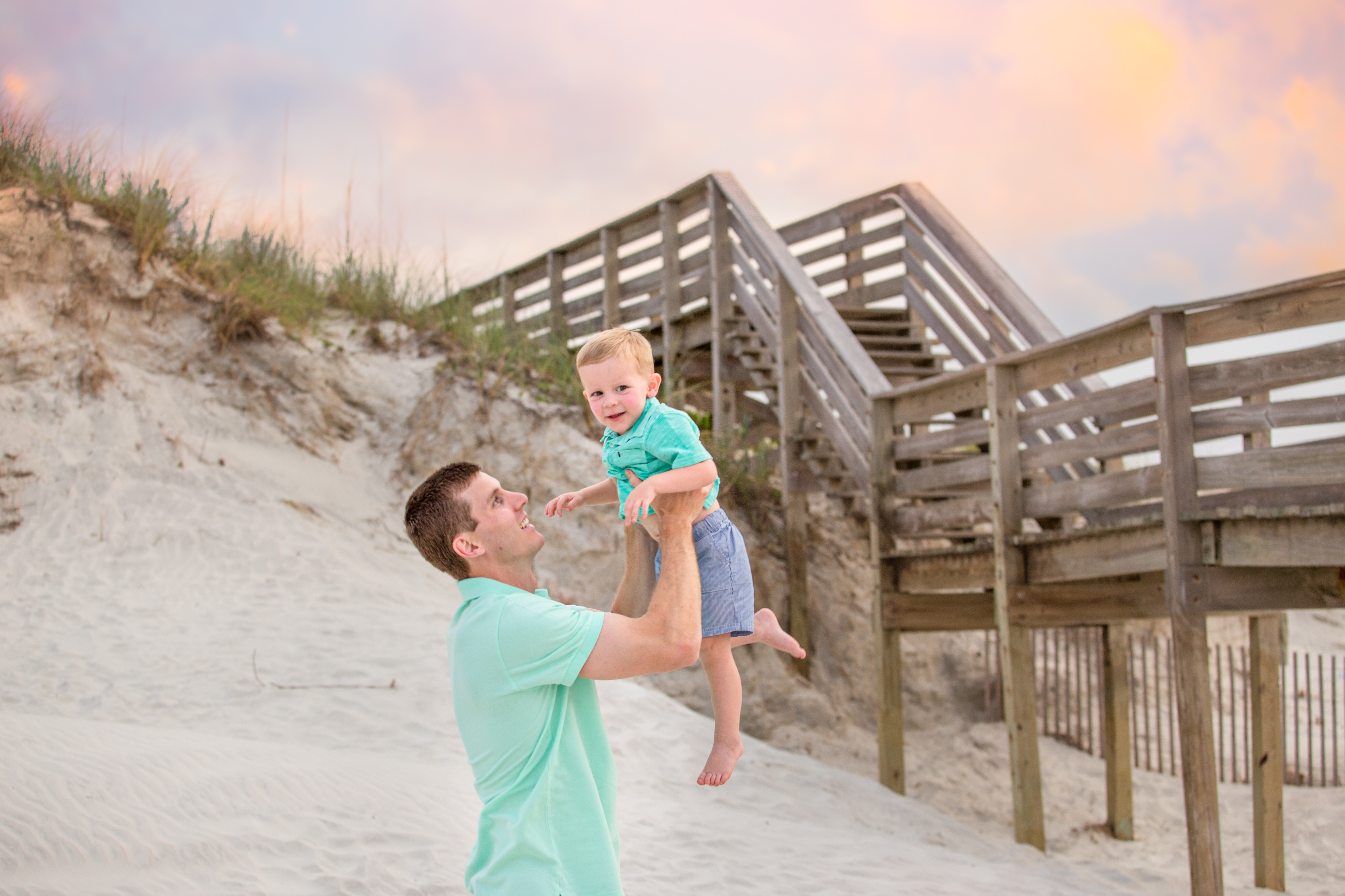 Father and sun play on the beach for family portraits by palm shores photographer