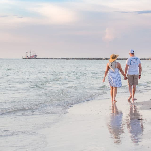 Clearwater photography of couple walking along the beach at sunset