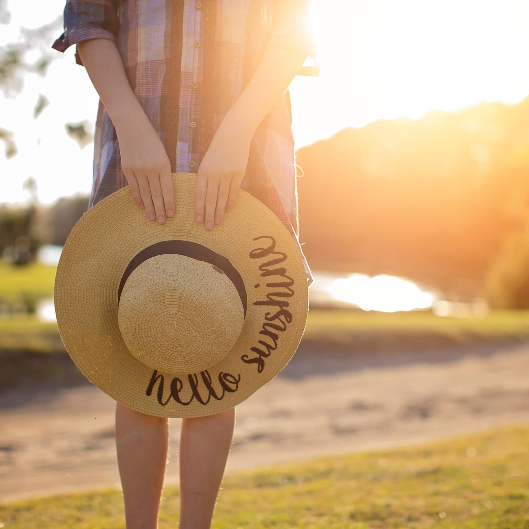 Stock image of girl holding sun hat with a sun flare in the background for a blog about escaping to little Gasparilla Island