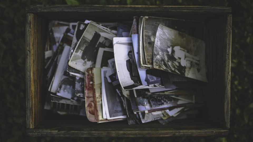 Orlando family photographers post about photo storage with an image of old photographs in a box